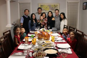 """This family photo is from IP Paralegal, Gianella Domdom. """"We prepared the turkey using the brown-sugar glaze recipe from Martha Stewart's web site - for the second year in a row. We love it! In addition to traditional Thanksgiving dishes like stuffing, cranberry sauce, roasted potatoes, and butternut squash, we also prepared two Filipino dishes - bibingka (a coconut-rice cake) and lumpia (egg rolls). The cranberry sauce recipe we used was also from the web site. https://www.marthastewart.com/316142/basic-cranberry-sauce https://www.marthastewart.com/863968/turkey-brown-sugar-glaze"""