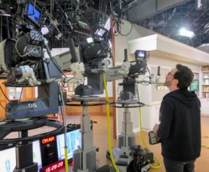Here is a behind the scenes look at one of the crew members checking one of the cameras on set.