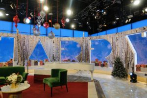The set is decorated in festive green and red surrounded by giant snowflakes for the holidays.