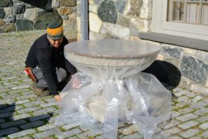 Because stone and cement can crack from exposure to the winter elements, Chhiring then covers the birdbath with heavy duty plastic. Rolls of this plastic can be ordered online or purchased at your local hardware and home supply store.