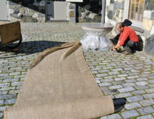 Chhiring cuts the burlap fabric to fit - one long piece that can completely wrap around the birdbath.
