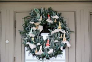 I love this merry wreath on my porch door - filled with miniature bottle brush trees and snow covered church ornaments.