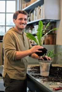 Here's Ryan repotting a bird's nest fern. Guests love walking through the greenhouse to see all the wonderful, healthy plants.
