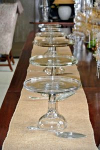 My large Brown Room dining table is getting set buffet style - a row of pretty cake stands are placed on a table runner.