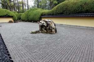 "Here is the Karesansui Late Rock Garden. Karesansui means ""dry landscape."" In this garden, rocks are arranged in a bed of raked gravel. The style was perfected at Zen Buddhist temples."