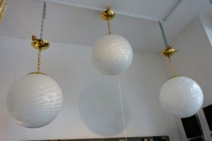 These are three 20th century Italian glass globe pendants with white swirl motifs. The chain ware is brass and each is about 15-inches wide.
