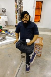 """Luis Flores, """"Morning Coffee"""", 2017, with yarn, clothes, Vans, Styrofoam cup and cinder block"""