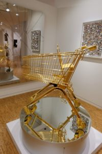 """Sylvie Fleury also created this piece, """"Serie Ela 75/K; Easy, Breezy, Beautiful"""" 2000. It's a 24-karat gold plated shopping cart with a plexiglass bar."""