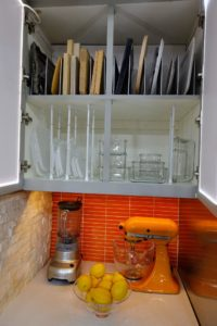 Here, I repurposed small adjustable curtain rods and file holders to create dividing storage spaces for container lids and cutting boards.