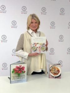 "The book signing was held in the Home Department. Macy's always sets up such a nice and inviting staging area surrounded by pieces from my various collections. I am holding a copy of ""Newlywed Kitchen"" with ""Slow Cooker"" and ""Martha's Flowers"" on the table."