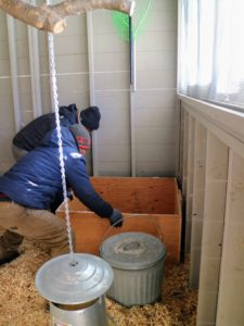 Pete and Phurba move one nesting box into the coop - it fits perfectly in this corner.