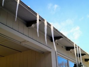 Hanging from the roof are several long icicles. Icicles form on days when the outdoor air temperature is subfreezing and sunshine warms and melts some snow or ice. Then, as it drips off the roof, a water droplet freezes when it loses its heat to the cold air.