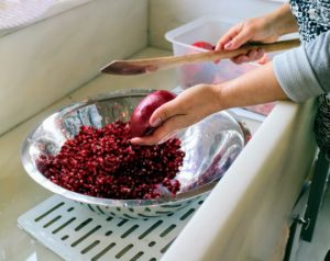 Sanu holds the fruit - seeds side in the palm of her hand - and using a large wooden spatula, or spoon, taps the back of the pomegranate.