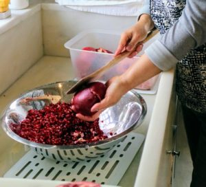 Sanu likes to tap the center of the back of the pomegranate first to loosen the seeds, and then tap the sides until the seeds fall out into a deep, wide bowl.