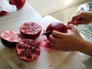 With a sharp knife, Sanu gently cuts each fruit in half, crosswise.