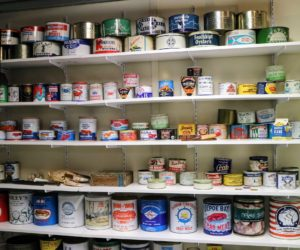 The museum is housed in a converted two-car garage. An entire wall of shelves features a collection of colorful vintage tins in various sizes, showing how oysters were sold over the years.