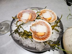 This dish includes queen scallops from Nordskott, in the Northern Barents Sea. The scallops are served on a bed of ice and seaweed.