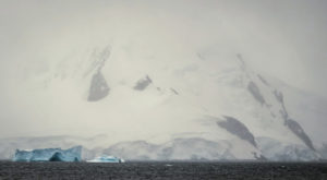 All these photos are taken from our ship - the blue iceberg looks so small in front of the massive mountains behind it.