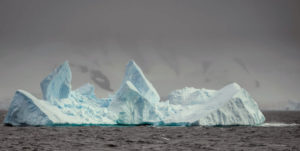 The Gerlache Strait is filled with spiky blue icebergs, snow and mountains.
