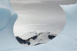 Dr. Knapp looked through a crack in this section of an iceberg to photograph the mountains beyond.