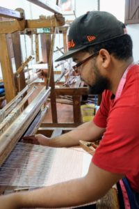 Here is a weaver working in one of the village studios.