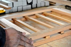 In between the two frames, Pete places six smaller wooden slats evenly spaced across the structure. Doing this helps to make it more sturdy. Pete then lines up all the pieces perfectly.