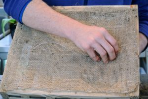 Using a piece of monofilament, or fishing line, Ryan strings it through the burlap and around two or three of the middle slats.