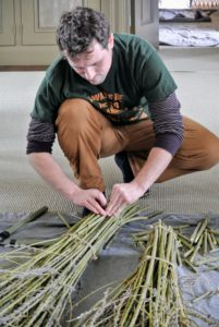 Once they are gathered, Ryan and Wilmer tie the bunches together with jute twine. Here, Ryan makes sure the twine is snug.