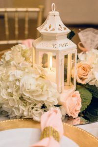 Each table centerpiece included a single lantern surrounded by flowers in cream and soft pastel peach. (Photo by Joseph Shkreli)