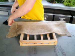 Ryan then folds the burlap in half to make a pocket and fits it over the frame.