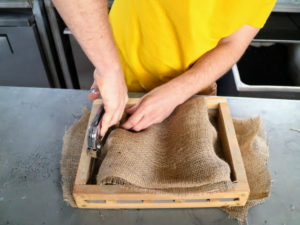 Ryan then tucks the sides into the frame and using a staple gun, secures the burlap onto the wooden mount.