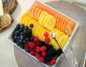 Here is a tray of fresh berries, cantaloupe and pineapple beautifully arranged on a white tray.