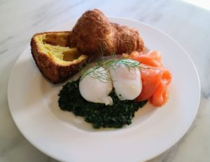 Here is a plate with a popover, creamed spinach poached eggs and salmon.