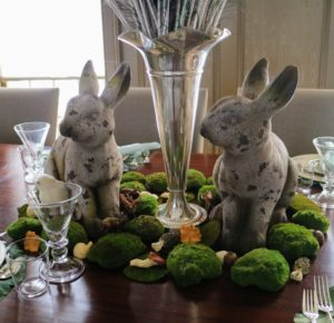 Underneath the vase of peacock feathers, antique bunnies watch over the table.
