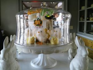 Under this dome, more chicks. Surrounding the cake stand are porcelain figural bunnies.