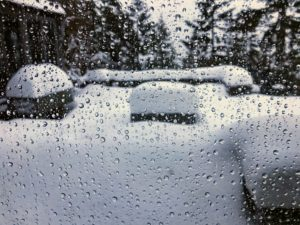 Droplets of melted frost and dripping snow cover this window pane.