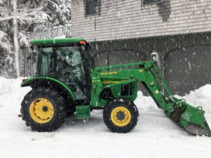 Here is Rick driving our trusted John Deere tractor the following morning. The tractor's front end loader bucket is helpful for carrying snow out of the way.