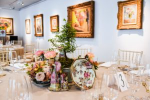 This bonsai is decorated with a Chinese export Famille Rose porcelain dinner service, which includes two smaller tureens, and one large tureen, two bowls, and two pairs of 18th century Chinese export candlestick holders. Ranunculus flowers are also part of this tablescape. (Photo by BFA Photographer, Joe Schildhorn)