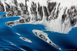 In this image, Seth looked down to find a reflection that distorted the subject into abstraction. The Gullet is north of the Adelaide Islands and Marguerite Bay off the West Coast of the Antarctic Peninsula. It is rarely traveled as it is usually blocked by icebergs and sea ice. This area is known for stunning glacial scenery and large tabular icebergs derived from the Ross Ice Shelf.