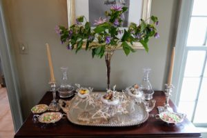 "A small vase of colorful clematis were placed on this table in my ""bird room"". Delicate bird nests filled with eggs sit on the silver serving tray."