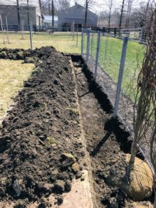 A trench about a foot deep is dug along the fence line.