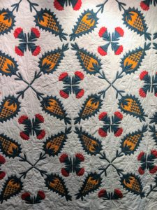 Here is a yellow, blue and red applique Pineapple Rose quilt, American 1840 to 1855.