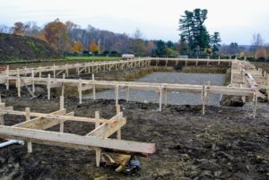 Once the site was dug out, the pool shape is created using stakes and wood forms. The forms show the outer edge of the pool shell.