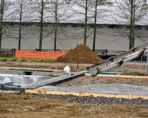 After the frame is complete, the concrete is poured for the base. The spout is first positioned in a corner of the pool and then guided lengthways to the opposite corner.