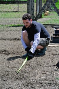Ryan measures each of the beds to make sure the three planned trenches in each bed are equally spaced.
