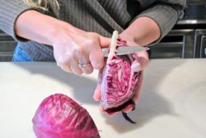 Next, Shqipe removes the core of the cabbage. The cabbage is so fresh and colorful.