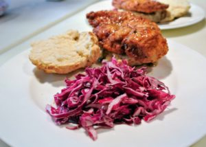 The chicken, biscuit and slaw are plated, and the pepper-honey sauce is drizzled over the chicken.