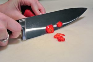 Shqipe starts by slicing the Fresno chile crosswise into rings.