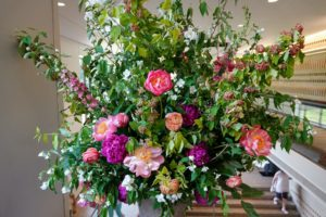 """""""Art in Bloom"""" is when florists are invited to create beautiful displays interpreting artwork in the Museum's collection. This display includes Mock Orange, Coral Charm peonies, and ranunculus. It was designed by Sara Ward at Wildflowers."""