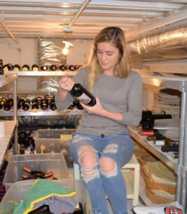 Shqipe looks at each label to make sure the bottle goes in the right place - reds on one side, whites on another, all in chronological order by vintage year.